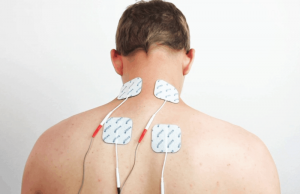 TENS pads on the upper back for pain relief.